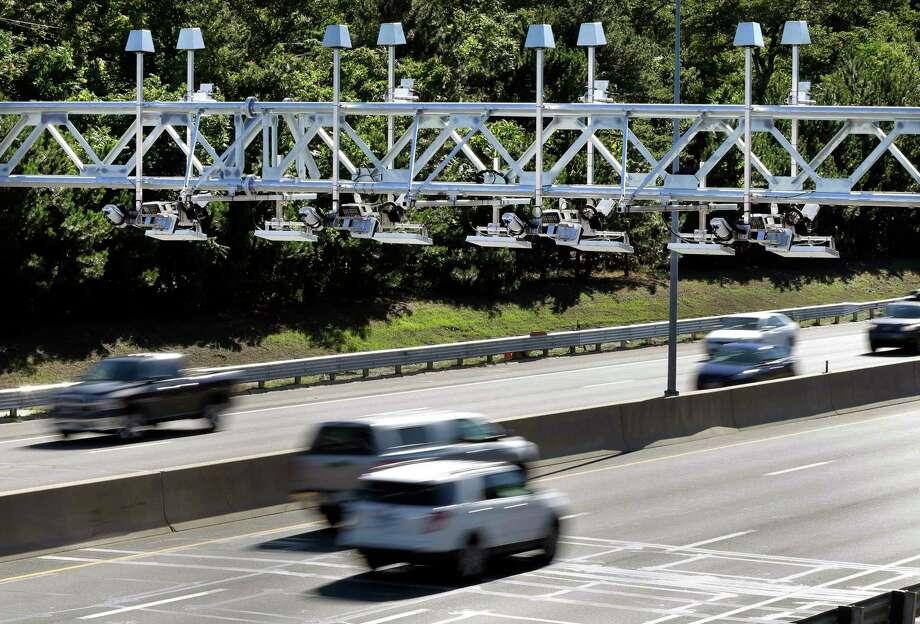 Cars pass under toll sensor gantries hanging over the Massachusetts Turnpike in Newton. Photo: Elise Amendola / Associated Press File Photo / AP