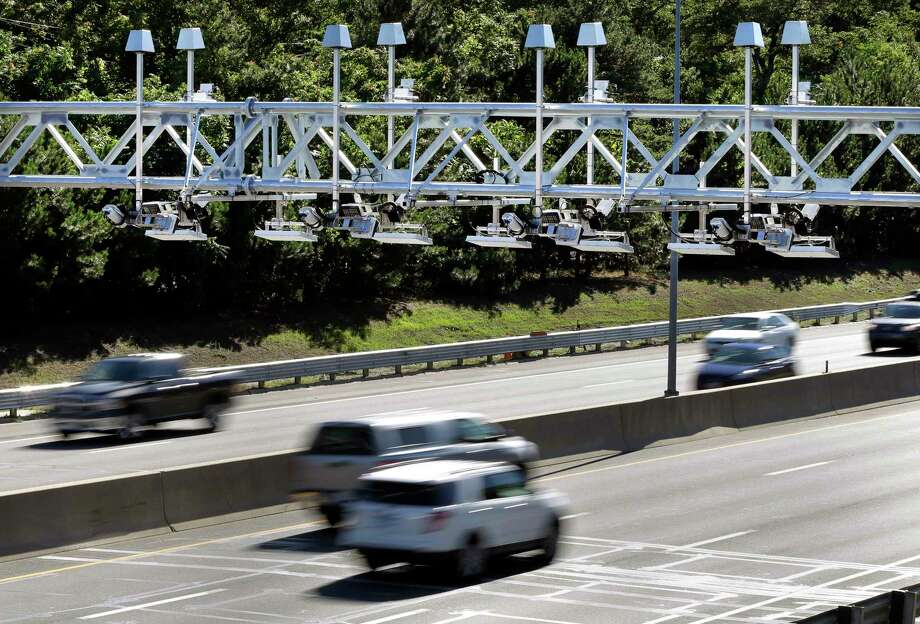 Cars pass under toll sensor gantries hanging over the Massachusetts Turnpike in Newton. Photo: Elise Amendola / Associated Press File Photo / AP