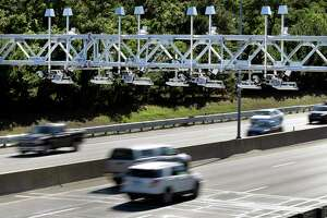 Cars pass under toll sensor gantries hanging over the Massachusetts Turnpike in Newton.