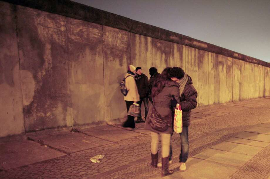 Tourists visit the remains of the Berlin Wall at the eve of the 20th anniversary of the fall of the Berlin Wall Nov. 8, 2009. A reader disputes comparisons between this wall and what the president proposes at the U.S./Mexico border. Photo: Markus Schreiber /ASSOCIATED PRESS / AP2009
