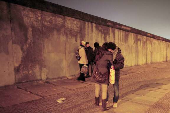 Tourists visit the remains of the Berlin Wall at the eve of the 20th anniversary of the fall of the Berlin Wall Nov. 8, 2009. A reader disputes comparisons between this wall and what the president proposes at the U.S./Mexico border.