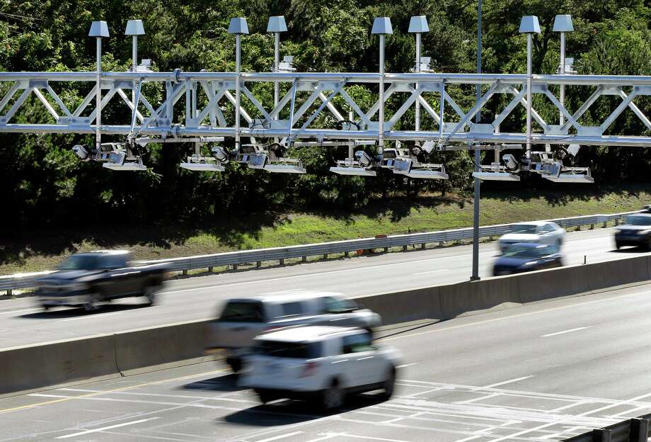 In a file photo, cars pass under toll sensor gantries hanging over the Massachusetts Turnpike. Photo: AP Photo /Elise Amendola / AP / AP