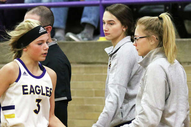 CM's Tori Standefer (right) and Hannah Sontag (middle) welcome teammate Kelbie Zupan back to the bench.