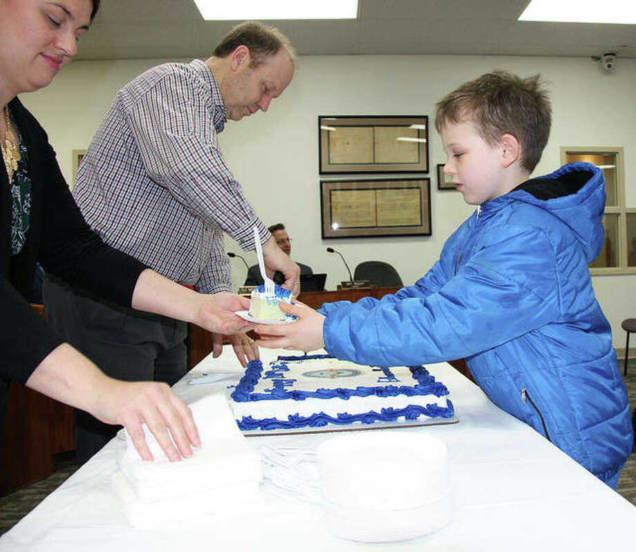 Cooper Hotson, 8, right, receives the first piece of Edwardsville's bicentennial cake from City Clerk Jeanne Wojcieszak during Tuesday's city council meeting as City Treasurer Rich Hampton continues cutting the baked good into pieces. Edwardsville received its charter on Feb. 23, 1819. Photo: Charles Bolinger | The Intelligencer