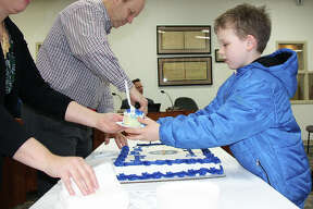 Cooper Hotson, 8, right, receives the first piece of Edwardsville's bicentennial cake from City Clerk Jeanne Wojcieszak during Tuesday's city council meeting as City Treasurer Rich Hampton continues cutting the baked good into pieces. Edwardsville received its charter on Feb. 23, 1819.