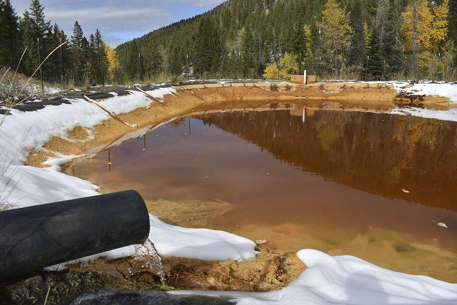 Water contaminated with arsenic, lead and zinc flows last year from a silver mine into a holding pond near Rimini, Mont. The waste is poisoning aquatic life and tainting drinking water. Photo: Matthew Brown / Associated Press 2018
