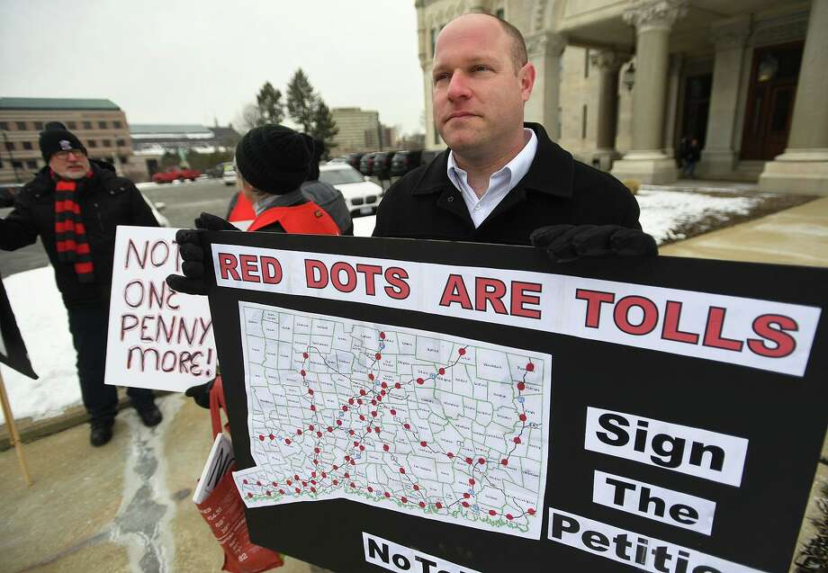 Patrick Sasser, of Stamford, and protestors from the group No Tolls CT, hold signs outside the Capitol in Hartford on February 20. Governor Ned Lamont has proposed tolls on state highways to pay for transportation improvements. Photo: Brian A. Pounds / Hearst Connecticut Media / Connecticut Post