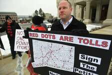 Patrick Sasser, of Stamford, and protestors from the group No Tolls CT, hold signs outside the Capitol in Hartford on February 20. Governor Ned Lamont has proposed tolls on state highways to pay for transportation improvements.