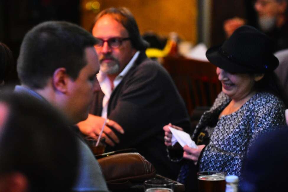 Caroline Isachsen, in hat, who is known by her stage name MotherJudge, sits at McGeary's Pub in  Albany on Jan. 9, 2019, during the Best Damn Open Mic Ever, which she has hosted for years. Her husband and co-host, Sten Isachsen, is at center.
