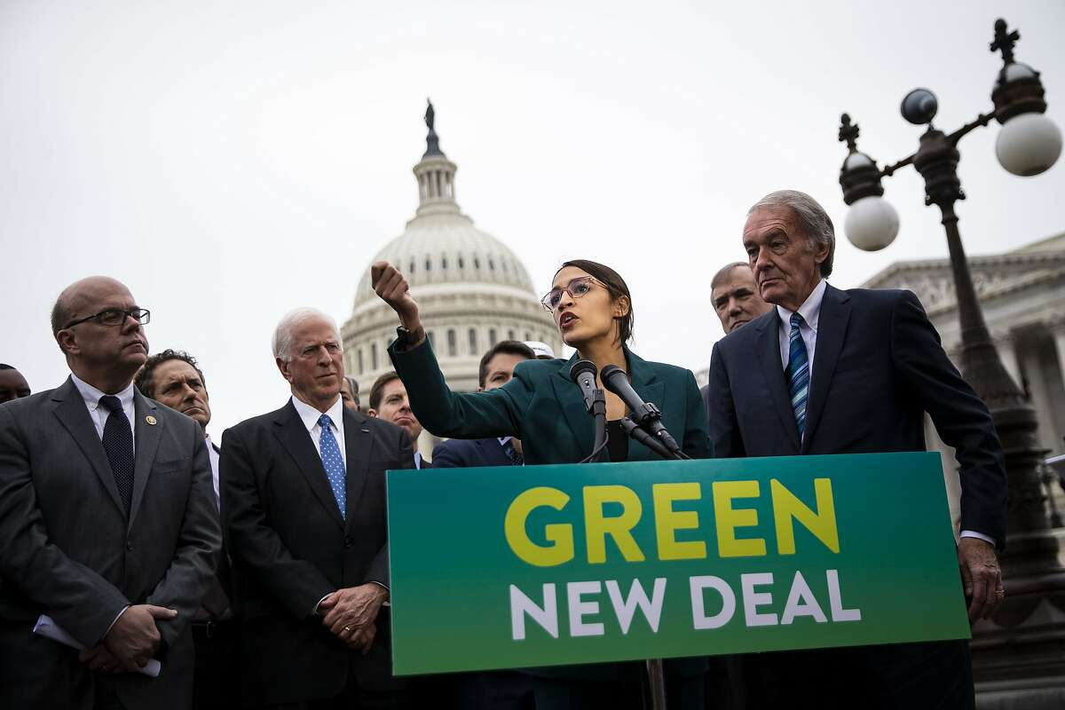 Representative Alexandria Ocasio-Cortez, a Democrat from New York, speaks as Senator Ed Markey, a Democrat from Massachusetts, right, listens during a news conference announcing Green New Deal legislation in Washington, D.C., U.S., on Thursday, Feb. 7, 2019. A sweeping package of climate-change measures unveiled Thursday by Ocasio-Cortez drew a tepid response from House Speaker Nancy Pelosi who didn't explicitly throw her support behind the measure. Hundreds of students from around the Bay Area are planning to walk out of school on Friday to demand urgent action on climate change.