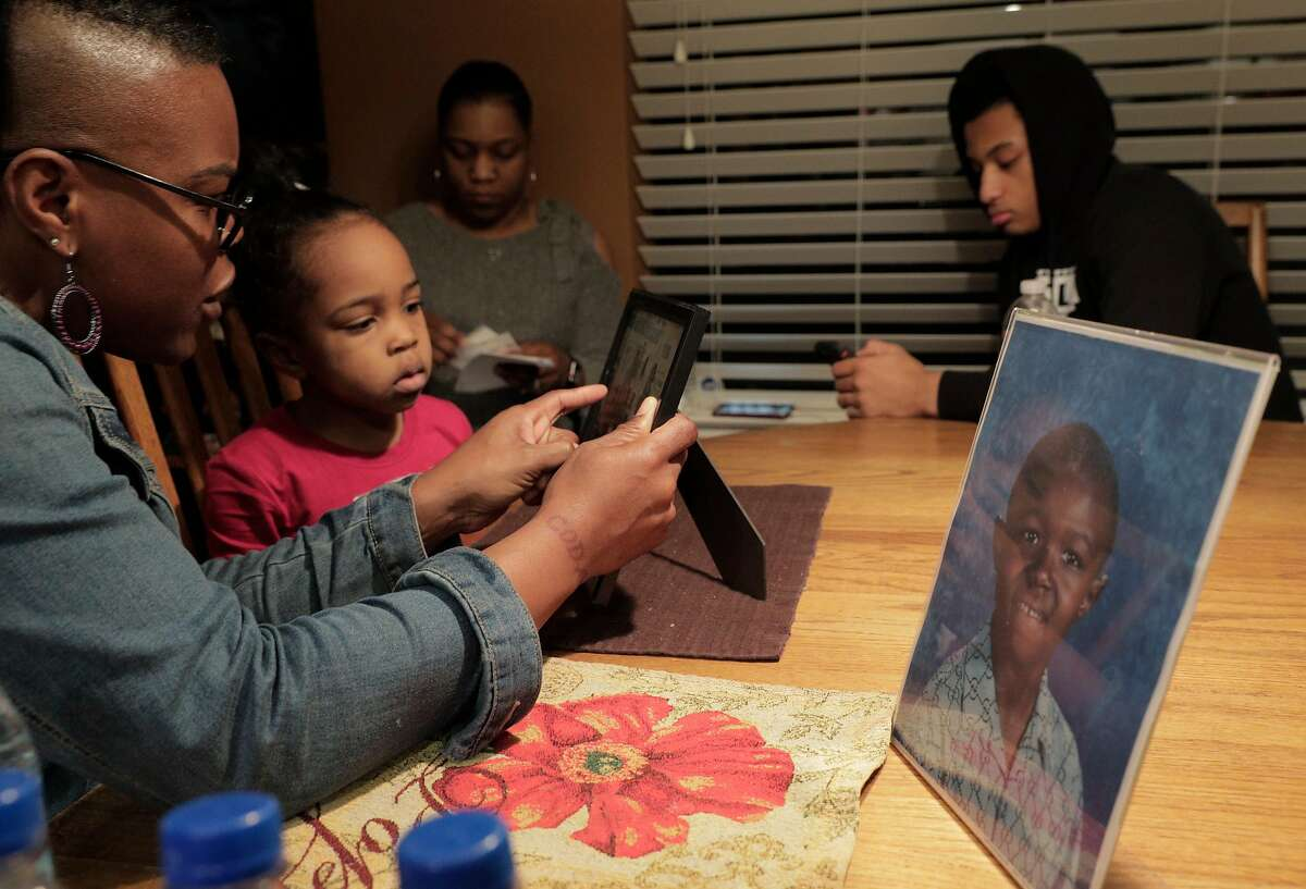 Clara McCoy, sister-in-law of Willie McCoy, shows pictures of Willie to Peyton McCoy, 3, center, at the home of Kori McCoy, in Hercules, Calif., on Thursday, February 14, 2019. The family of Willie McCoy, who was shot and killed by Vallejo Police officers as he woke up from sleeping in his car at a Taco Bell restaurant, gathered for press conference to address their issues with how their loved one was killed.