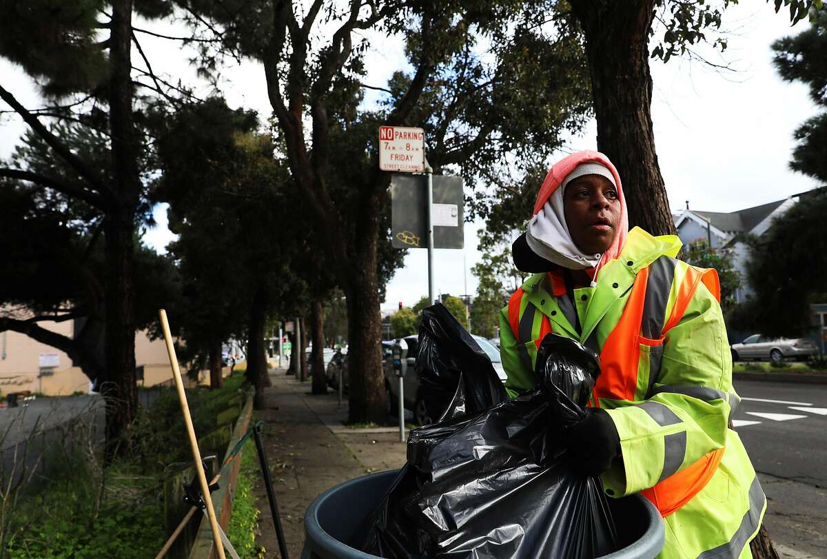 """Evette Demings, a Corridor Ambassador for the Department of Public Works, lifts a trash bag from a can after cleaning a section of Diamond St. in San Francisco, Calif., on Thursday, February 14, 2019. Corridor Ambassadors, a city program, hires people to clean specific, high traffic blocks around business corridors. """"The more I clean, the more I notice patrons and merchants actually helping out as well; cleaning in front of their store front, picking up garbage or even throwing it out instead of throwing it on the ground,"""" Demings said. """"I like people. I like working outside and I'm happy that my work shows for them and they appreciate it."""""""