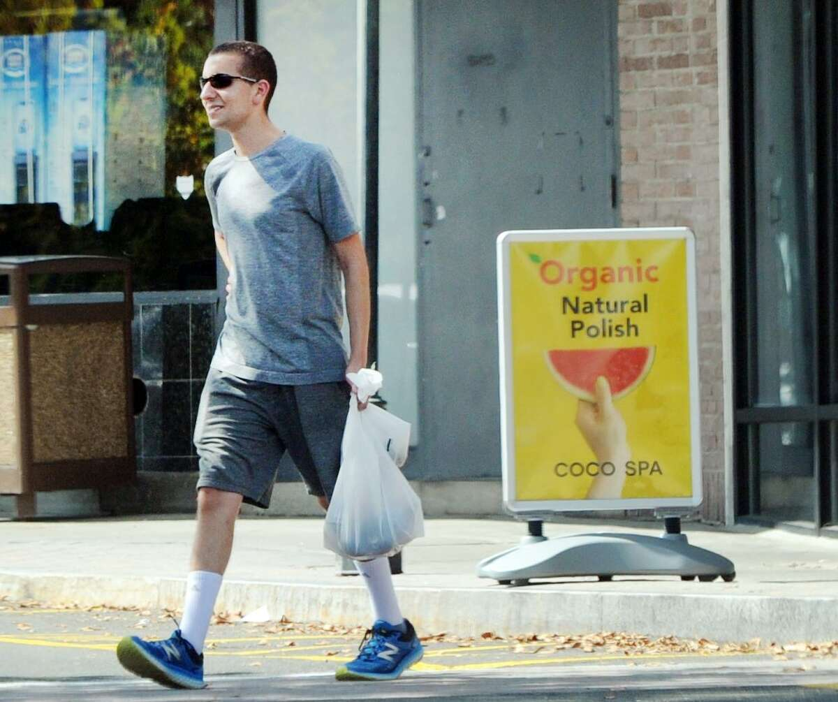 A customer carries a plastic shopping bag as he leaves the Riverside Commons Shopping Center in Greenwich prior to that town's ban going into effect.