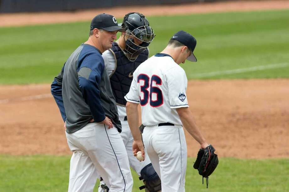 Milford's Josh MacDonald, left, pays a mound visit to a UConn hurler. MacDonald is in his eighth season as the Huskies' pitching coach. Photo: UConn Athletics