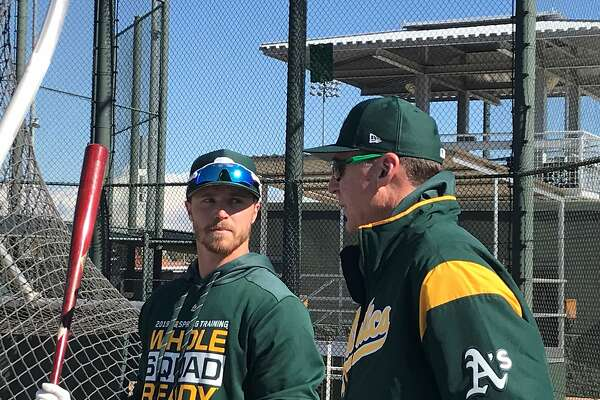 A's minor-leaguer Skye Bolt, left, chats with manager Bob Melvin during batting practice in Mesa, Ariz.