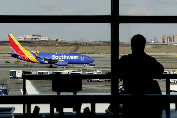 FILE- In this Jan. 25, 2019, file photo a Southwest Airlines jet moves on the runway as a person eats at a terminal restaurant at LaGuardia Airport in New York. Southwest Airlines is lashing out at the union representing its mechanics and suggesting that workers are purposely grounding planes to gain leverage in negotiations over a new contract. Southwest had canceled more than 400 flights, 10 percent of its schedule, by midmorning Wednesday, Feb. 20. (AP Photo/Julio Cortez, File)