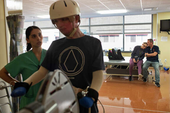 DJ Sutterfield and Karl Sutterfield wait as their son, Zachary Sutterfield, exercises with physical therapist Sarah Flores, left, during his daily rehabilitation session at the U.S. Army Institute of Surgical Research Burn Center.