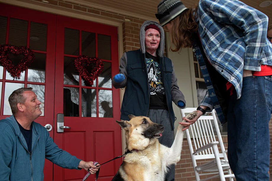 Zachary Sutterfield reacts as his older brother, Danny Sutterfield, right, shows tricks he has taught Zachary's dog, Moonshine. Danny has been caring for Moonshine while Zachary recovers and brought her to visit from San Angelo on Feb. 9, 2019. At left is their father, Karl Sutterfield. Photo: Lisa Krantz / San Antonio Express-News
