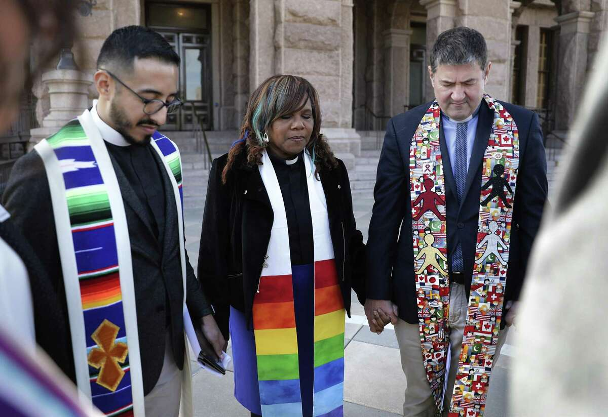 Rev. Dr. Michael Diaz of Dallas, left to right, Rev. Naomi L. Brown of San Antonio, and Rev. Andries Coetzee of San Antonio hold hands with other clergy in prayer as faith leaders from Austin, San Antonio, and Dallas gather to speak against the growing efforts to turn religion into a license to discriminate, and calling for laws that treat everyone including LGBTQ Texans, with equality, fairness and respect, at the State Capitol in Austin, TX, on Wednesday, Feb. 20, 2019.