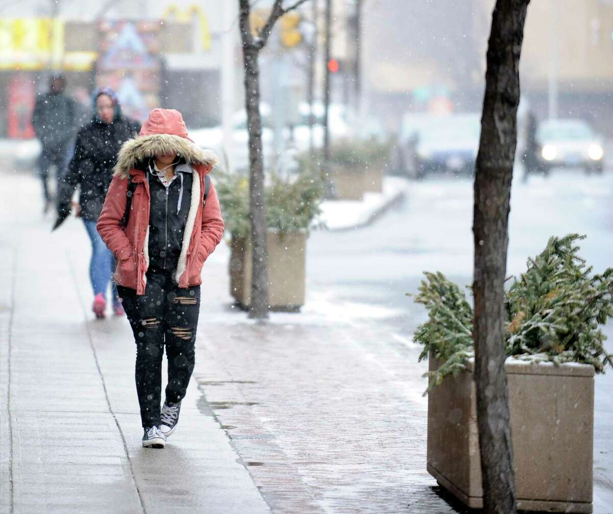 A pedestrian bundles up as light snow fall begins to fall on Wednesday, Feb. 20, 2019 in Stamford, Connecticut. Area residents can expect 2-4 inches of a wintry mix, changing over to ice and rain, making travel difficult in the region.