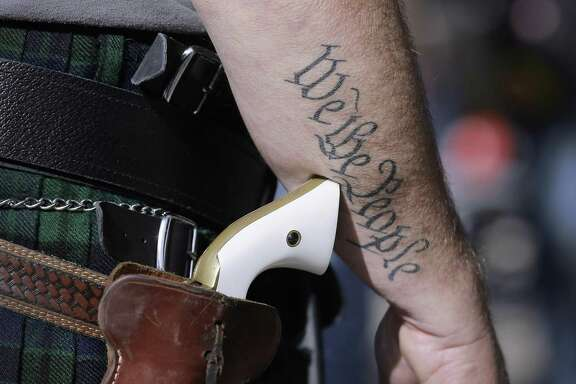 A supporter of open carry gun laws prepares for a rally in Austin in 2015. A reader disagrees with the latest Texas gun bill, scoffing at its premise.
