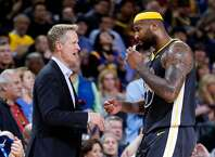 Golden State Warriors' head coach Steve Kerr greets DeMarcus Cousins as he removes Cousins late in 4th quarter of Warriors' 115-108 win over Utah Jazz in NBA game at Oracle Arena in Oakland, Calif., on Tuesday, February 12, 2019.