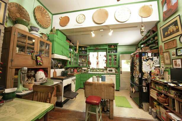 The kitchen is painted parrot green after Michaele Hayne's favorite bird. It has a jungle's worth of parrot paintings on baskets, and parrot advertisements.