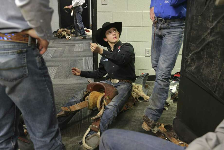 Stetson Wright (center) of Beaver, Utah spends time in the locker room chatting with his uncles as they work on adjusting their saddles for the saddle bronc riding competition at the San Antonio Rodeo on Wednesday, Feb. 20, 2019. Though Wright's family all compete in saddle bronc, the 19-year-old has chosen the path of bull riding instead. (Kin Man Hui/San Antonio Express-News) Photo: Kin Man Hui, Staff Photographer / San Antonio Express-News / ©2019 San Antonio Express-News