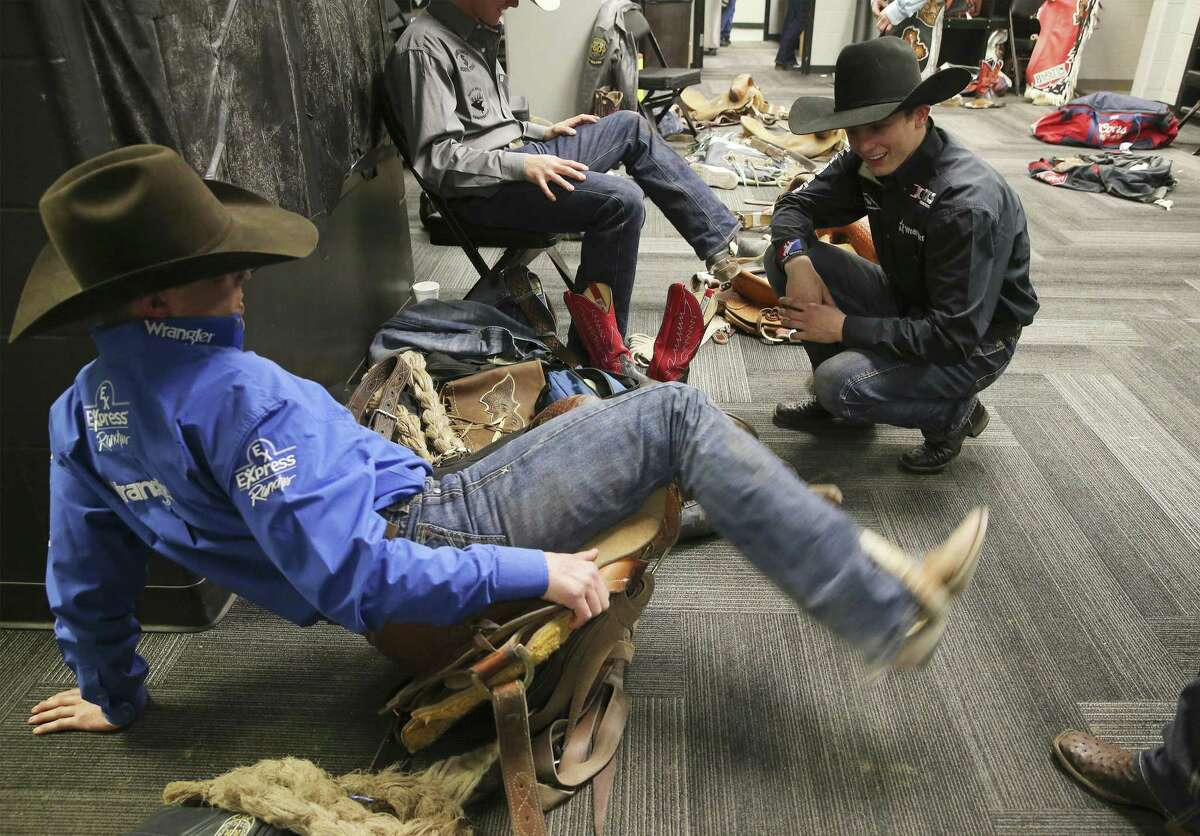 Stetson Wright (right) of Beaver, Utah spends time in the locker room chatting with his uncle Spencer Wright as they work on adjusting a saddle for the saddle bronc riding competition at the San Antonio Rodeo on Wednesday, Feb. 20, 2019. Though Wright's family all compete in saddle bronc, the 19-year-old has chosen the path of bull riding instead. (Kin Man Hui/San Antonio Express-News)