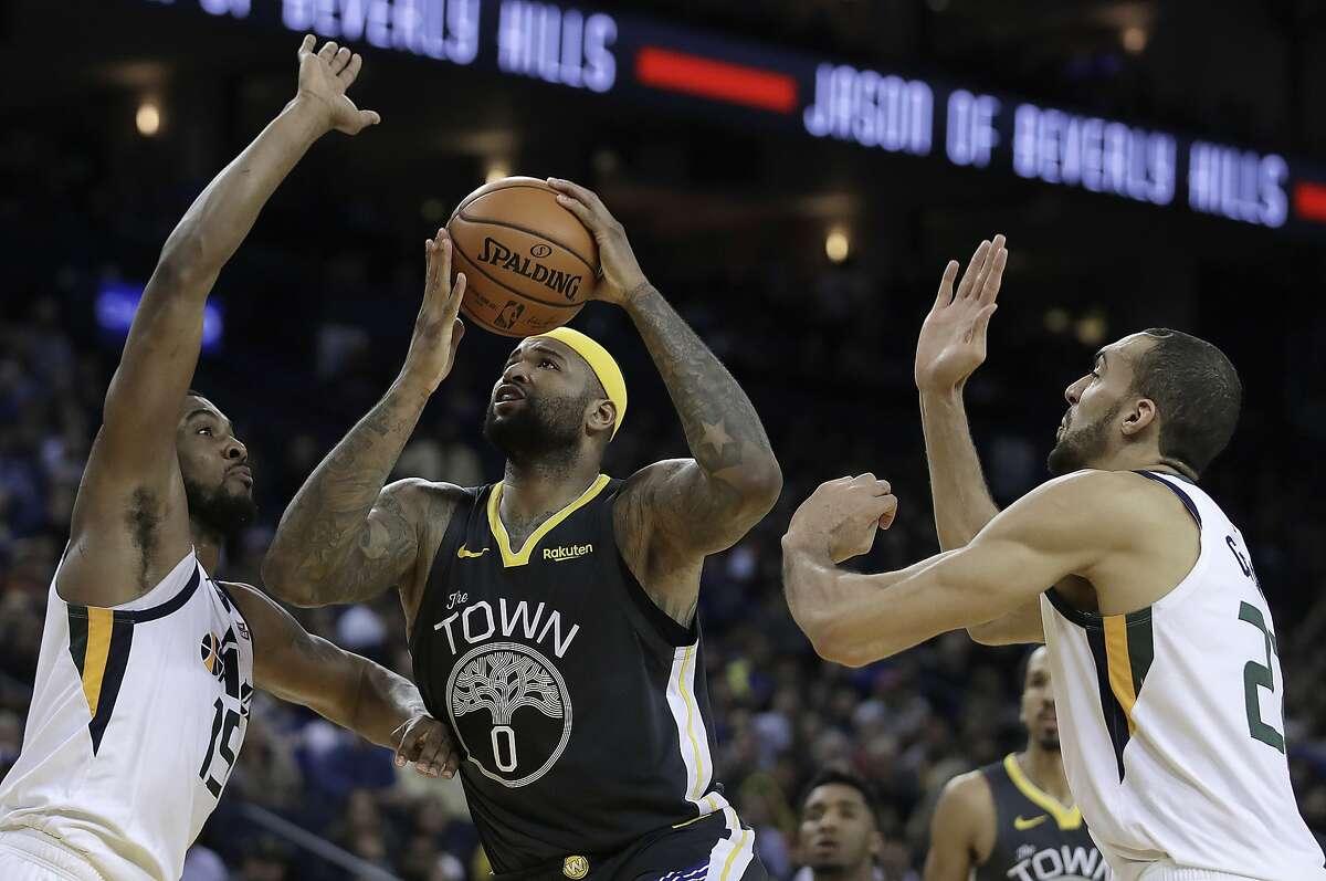 Golden State Warriors' DeMarcus Cousins, center, shoots between Utah Jazz forward Derrick Favors, left, and Rudy Gobert during the second half of an NBA basketball game Tuesday, Feb. 12, 2019, in Oakland, Calif. (AP Photo/Ben Margot)