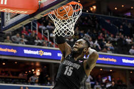 Georgetown center Jessie Govan strikes a pose as he dunks during the final minutes of the Hoyas' win over the Villanova Wildcats at Capital One Arena in Washington on Wednesday, Feb. 20, 2019.