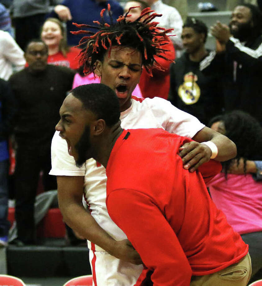 Alton assistant coach Aaron Womack (front) and the Redbirds' Moory Woods celebrate Wednesday night's SWC victory over Belleville West. Photo: Greg Shashack / The Telegraph