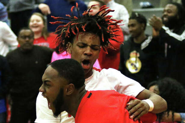 Alton assistant coach Aaron Womack (front) and the Redbirds' Moory Woods celebrate Wednesday night's SWC victory over Belleville West.