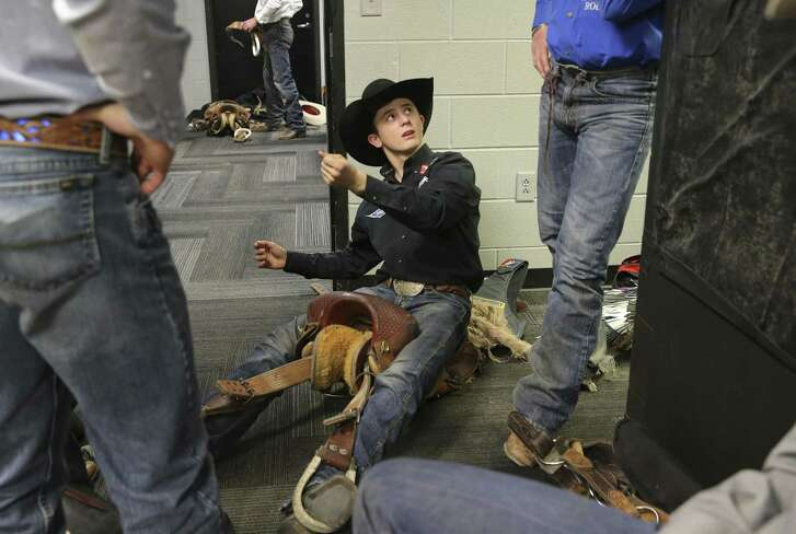 Stetson Wright of Beaver, Utah, talks with his uncles as they work on adjusting their saddles for saddle bronc riding.