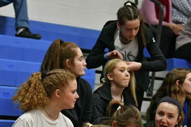 A couple of Hoosick Falls players fix the hair of their teammates before they take on Hoosic Valley in a Class C girls' quarterfinal on Wednesday, Feb. 20, 2019 in Schaghticoke, N.Y. (Lori Van Buren/Times Union)