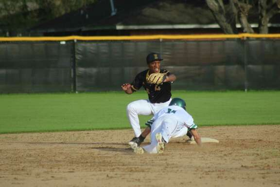 Pasadena's Victor Hinojosa dives back to the second-base bag, but the Eagle freshman was tagged out during second-inning play at Maguire Field Monday night as the Eagles and Aldine Eisenhower celebrated their season openers.
