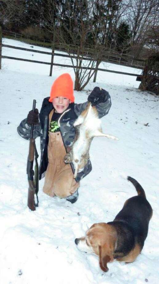 Below, three winters ago, then-12-year-old Hugh Walker of Cass City shows his first rabbit shot on the run, thanks in part to the help of the writer's beagle, 'Boomer.' (Tom Lounsbury/Hearst Michigan)