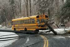 A school bus sliding on an ice patch on a curve in North Stamford struck a pole, bringing down power wires Thursday morning, Dec. 21, 2019. Concerned about the chance for electrocution, three students and the bus driver had to stay inside the bus for about a half hour before power could be cut off to the power lines draped over the bus.