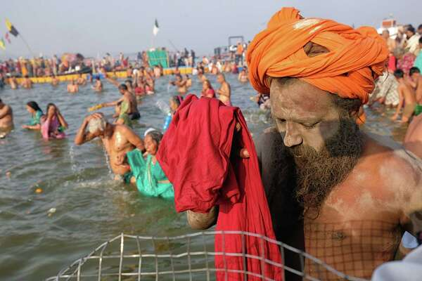 An Indian sadhu (Hindu holy man) takes a dip into the water at Sangam during the Kumbh Mela festival.