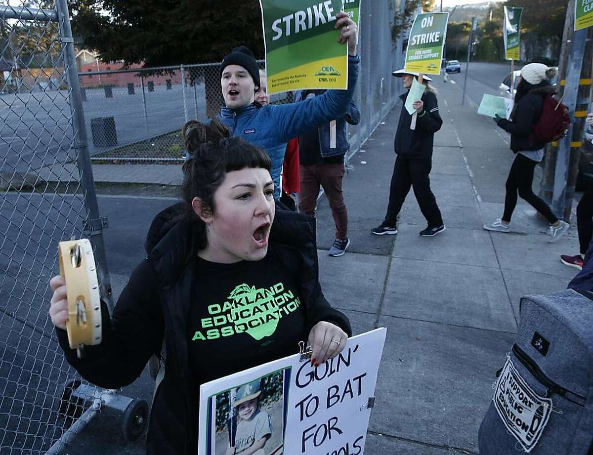Sixth grade teacher Gina Lozito leads a picket line chant at Claremont Middle School on the first day of the teachers strike in Oakland, Calif. on Thursday, Feb. 21, 2019.