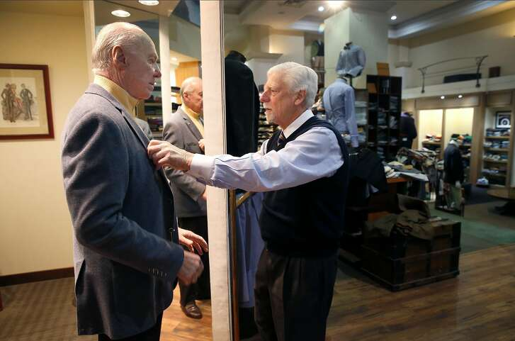Mike Blunden (right) helps Andre Baldanza try on a sportcoat at the Hound Gentlemen's Clothier store on Sutter Street in San Francisco, Calif. on Wednesday, Feb. 20, 2019. The longtime owners are retiring at the end of the month and may close the shop if they are unable to find a buyer.