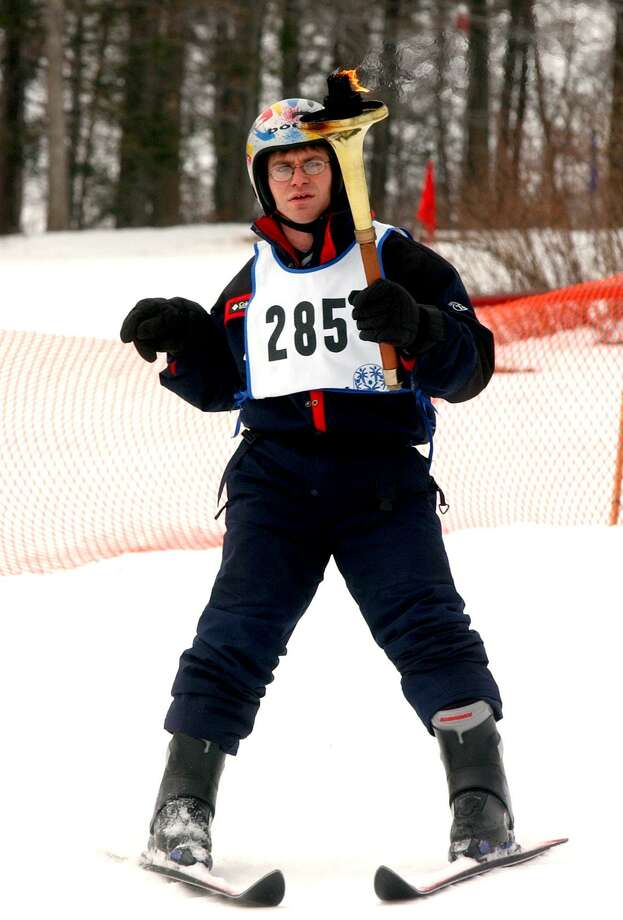 A Wallingford Special Olympics Connecticut athlete launches the winter games ceremony, skiing down the hills of Powder Ridge in Middlefield, holding the torch aloft. Photo: File Photo