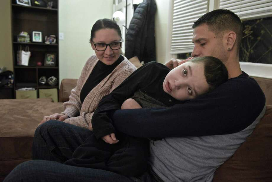 Above and below, Jared Carreras, 12, with his mother Shirley Correia and step-father Jayce Correia in their Brookfield home last week. Photo: H John Voorhees III / Hearst Connecticut Media / The News-Times