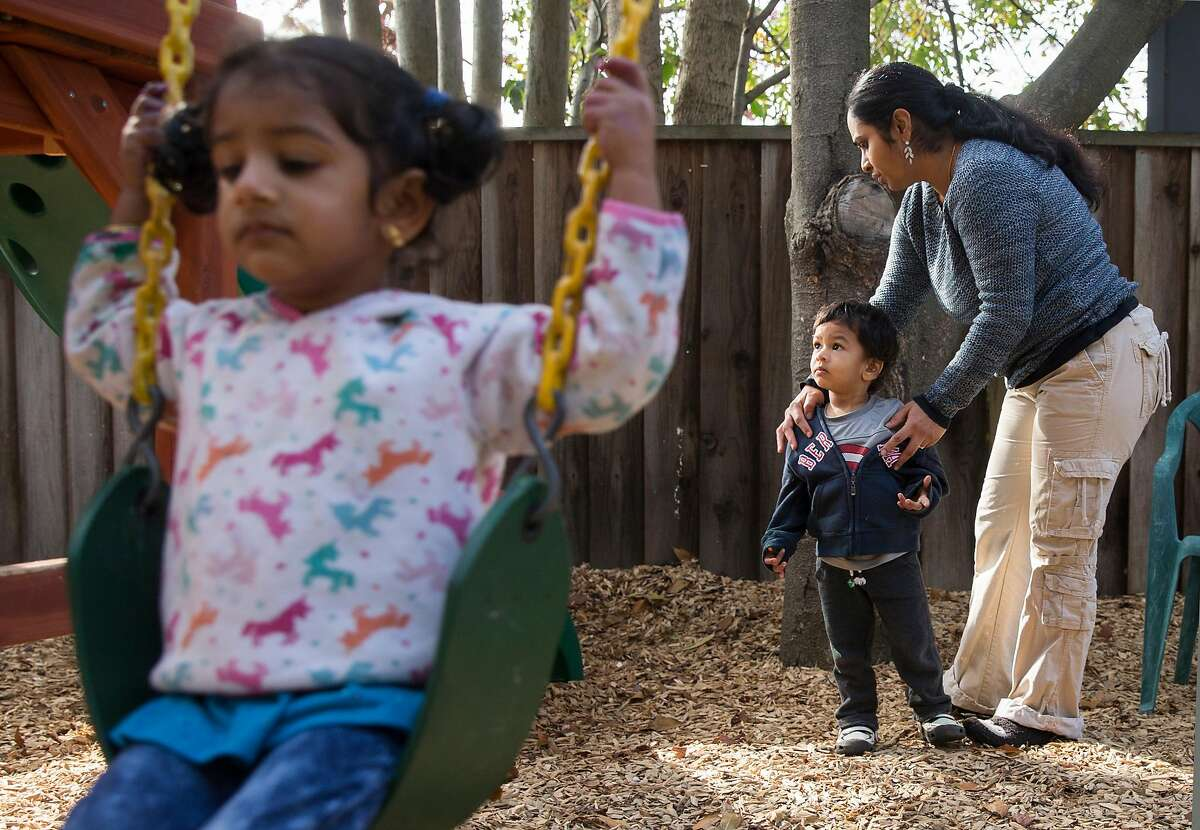 Renuka Sivarajan, center, helps Zayne, 2, while Mrudhla, 2, left, and Myra, 3, swing on the playground Wednesday, Jan. 17, 2018 at her home in Fremont, Calif.