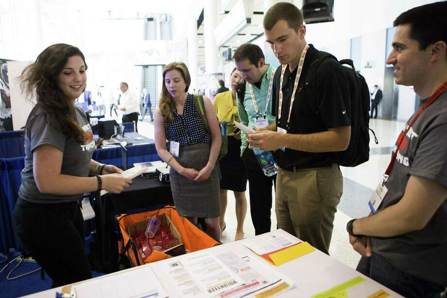 Mary Bianca, left, provides literature to Kelly Ratchinsky, Huajin Qu, Bernardo Huesca and Scott Rolling, right, at the United Against Human Trafficking booth at the 2016 Offshore Technology Conference, Wednesday, May 4, 2016, in Houston. ( Marie D. De Jesus / Houston Chronicle ) Photo: Marie D. De Jesus, Staff / Houston Chronicle / © 2016 Houston Chronicle