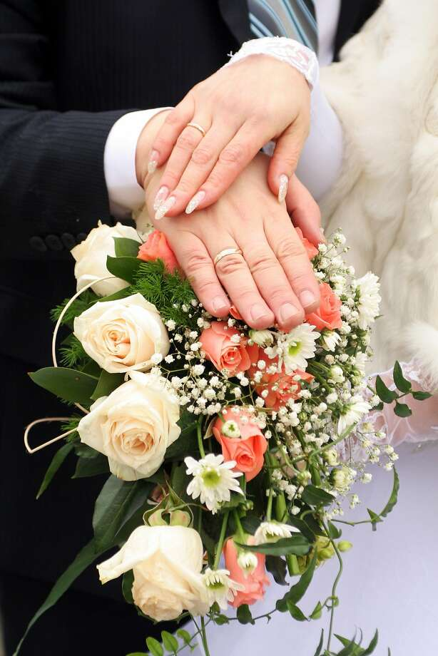 Two newlywed hands with gold rings over fllowers Photo: Willgame - Fotolia