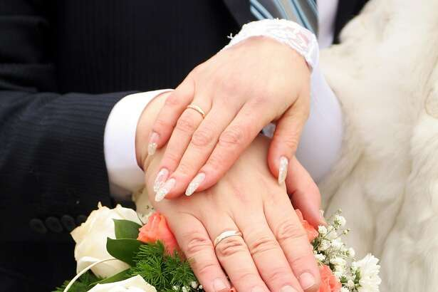 Two newlywed hands with gold rings over fllowers
