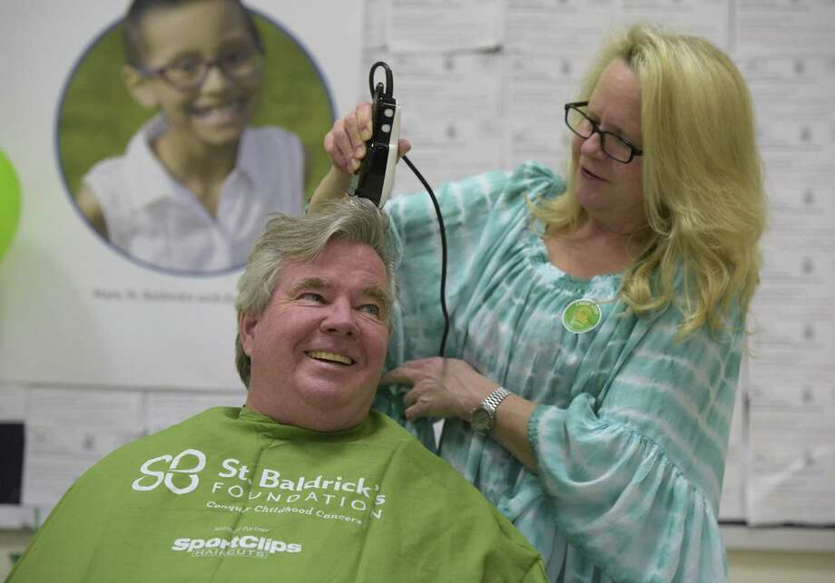 Brookfield First Selectman Stephan Dunn gets a buzz from hairdresser Jamie Lomedico MacMullen, of Brookfield, during a St Baldrick's Foundation fund raiser by the Peer Counseling group of Brookfield High School. St Baldrick's is a national organization that raises money for pediatric cancer research. Last year the event raised $10,000 dollars and they hope to meet or surpass that amount this year. Tuesday night, March 27, 2018, at Brookfield High School, in Brookfield, Conn. Photo: H John Voorhees III / Hearst Connecticut Media / The News-Times