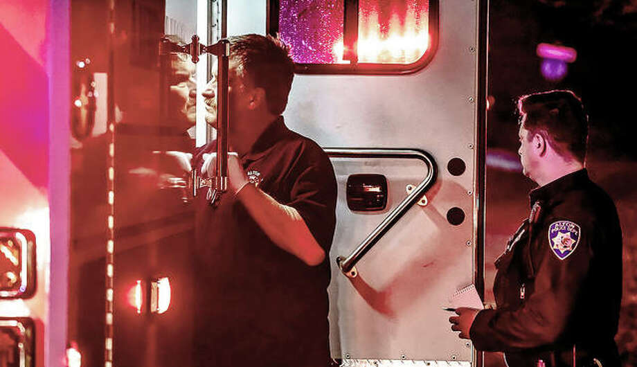 An Alton firefighter looks into an ambulance where paramedics treat the victim of a shooting during an apparent home invasion late Wednesday night. A police officer stands by with a pen and notebook. Photo: Nathan Woodside | The Telegraph