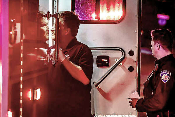 An Alton firefighter looks into an ambulance where paramedics treat the victim of a shooting during an apparent home invasion late Wednesday night. A police officer stands by with a pen and notebook.